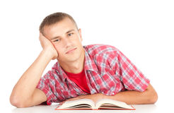 Male student with book leaning on the table Royalty Free Stock Photo