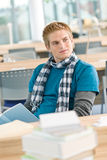 Male student with book sitting in classroom. Thoughtful male student with book sitting in classroom Stock Images