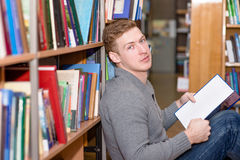 Male student with book sitting on floor in library Royalty Free Stock Images