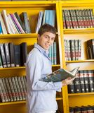 Male Student With Book Standing Against Shelf In. Side view portrait of happy male student with book standing against shelf in university library Royalty Free Stock Images