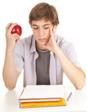 Male student with books and apple. Young male student with books and apple,white background, series Royalty Free Stock Photos