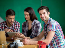 Male student on break at cafe. Young male student with friends on break at cafe Royalty Free Stock Image
