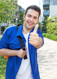 Male student on campus showing thumb up. Male student on campus laughing at camera and showing thumb up Royalty Free Stock Images