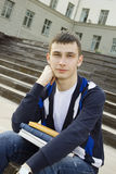 Male student on campus with textbooks. Closeup of an attractive male student on campus sits on the stairs with books Royalty Free Stock Photography