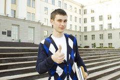 Male student on campus with textbooks. Thumbs up. Closeup of an attractive male student on campus sits on the stairs with books. Thumbs up Royalty Free Stock Photography