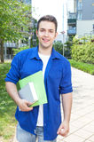 Male student on campus. Walking home and laughing at camera on a beautiful summer day Royalty Free Stock Photo