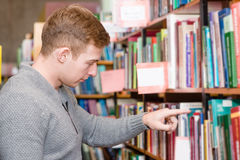 Male student chooses a book in the library Royalty Free Stock Photography