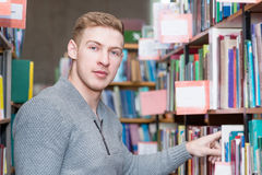 Male student chooses a book in the library Royalty Free Stock Image