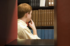 Male student choosing a book in the library Royalty Free Stock Photo