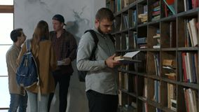 Male student choosing book on shelf in library stock footage