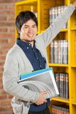 Male Student Choosing Books In College Library. Portrait of young male student choosing books in college library Stock Images