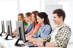 Male student with classmates in computer class. Education, technology, friendship and school concept - smiling male student with classmates in computer class Royalty Free Stock Photography
