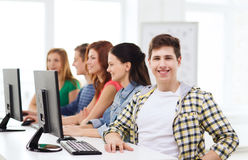 Male student with classmates in computer class. Education, technology, friendship and school concept - smiling male student with classmates in computer class Stock Image