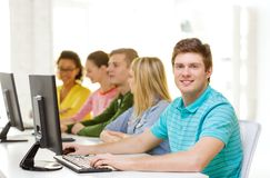 Male student with classmates in computer class. Education, technology and school concept - smiling male student with classmates in computer class Royalty Free Stock Photography