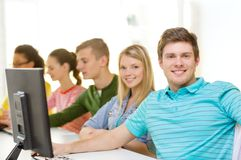 Male student with classmates in computer class. Education, technology and school concept - smiling male student with classmates in computer class Stock Images