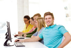 Male student with classmates in computer class. Education, technology and school concept - smiling male student with classmates in computer class Stock Image