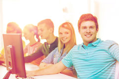 Male student with classmates in computer class. Education, technology and school concept - smiling male student with classmates in computer class Royalty Free Stock Photos
