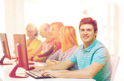 Male student with classmates in computer class. Education, technology and school concept - smiling male student with classmates in computer class Stock Photography