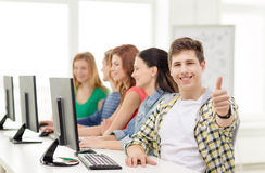 Male student with classmates in computer class. Education, technology and school concept - smiling male student with classmates in computer class at school Royalty Free Stock Image