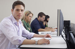Male Student With Classmates In Computer Lab. Portrait of male student with classmates in computer lab Stock Image