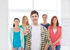 Male student with classmates showing thumbs up. Friendship, school and education concept - male student with classmates showing thumbs up gesture Royalty Free Stock Photography