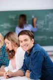 Male Student With Classmates And Teacher At Desk Stock Photography