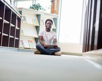 Male Student With Digital Tablet Sitting In. Full length portrait of African American male student using digital tablet while sitting on floor at library Stock Photography