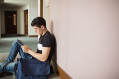 Male student with digital tablet sitting by wall. In corridor at college Royalty Free Stock Images