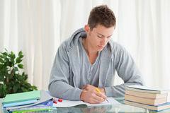 Male student doing his homework. In his house Royalty Free Stock Photography