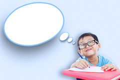 Male student and empty cloud speech. Image of male elementary school student studying and writes on the paper with empty speech bubble Royalty Free Stock Images