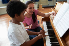 Male Student Enjoying Piano Lesson With Teacher Stock Photo