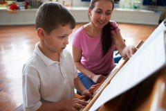 Male Student Enjoying Piano Lesson With Teacher Stock Image