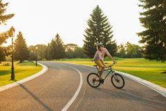 Male student enjoying riding bike. Young cheerful man cycling on country road, sunny day. People and healthy lifestyle Stock Photo