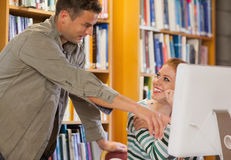 Male student explaining his classmate something on the computer. In library Stock Images