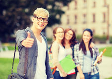 Male student in eyglasses showing thumbs up. Summer holidays, education, campus and teenage concept - smiling male student in black eyeglasses with group in the Stock Photo