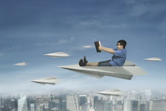 Male student flying with paper airplane. Picture of a male elementary school student flying above a city with a paper airplane and holding a book Stock Images