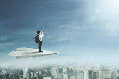 Male student flying with paper plane. Picture of a male student looking through a binoculars while flying with a big paper plane above a city Royalty Free Stock Image