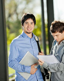 Male Student With Friend Reading Book In Campus. Portrait of confident male student with friend reading book in college campus Stock Images