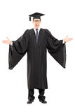 Male student gesturing with hands. Full length portrait of a male student in graduation gown gesturing with hands isolated on white background Stock Photography