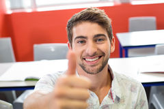 Male student gesturing thumbs up in classroom Royalty Free Stock Image