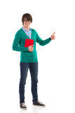 Male student giving thumb up. Smiling young man holding a book and showing thumb up. Full length studio shot isolated on white Royalty Free Stock Photography