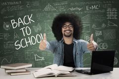 Male student giving thumbs up. Picture of a male college student giving thumbs up while sitting with scribbles on the chalkboard Stock Photography