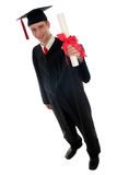 Male student graduating. Portrait of a man in graduation robes holding a diploma Royalty Free Stock Image