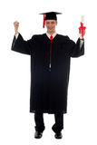 Male student graduating. Portrait of a man in graduation robes holding a diploma Stock Photo