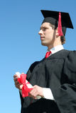 Male student graduating. Portrait of a man in graduation robes holding a diploma Royalty Free Stock Images
