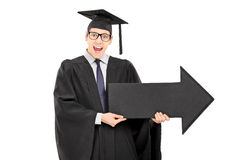 Male student in graduation gown holding big black arrow Stock Photo