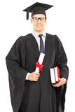 Male student in graduation gown posing with a diploma Stock Photography