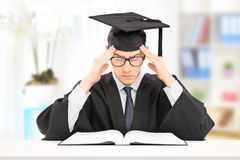 Male student in graduation gown studying indoors. Male student in graduation gown studying in a classroom Royalty Free Stock Image