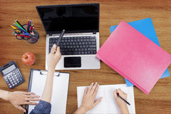 Male student hand pointing at laptop. Close up of male student hand pointing at the laptop screen while studying with his friend using book and stationery Stock Images