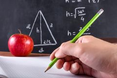 Male student hand writes in notebook with green wooden pen. Man student hand writes in blank notebook with green wooden pencils. Red apple and blackboard is Royalty Free Stock Photography